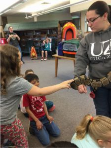 student touches snake held by handler
