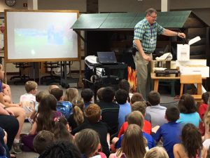 students watch as Mr. Westman lifts a bee tray from a box