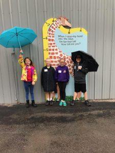 kids stand by giraffe poster