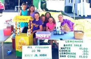 group of girls pose at lemonade stand