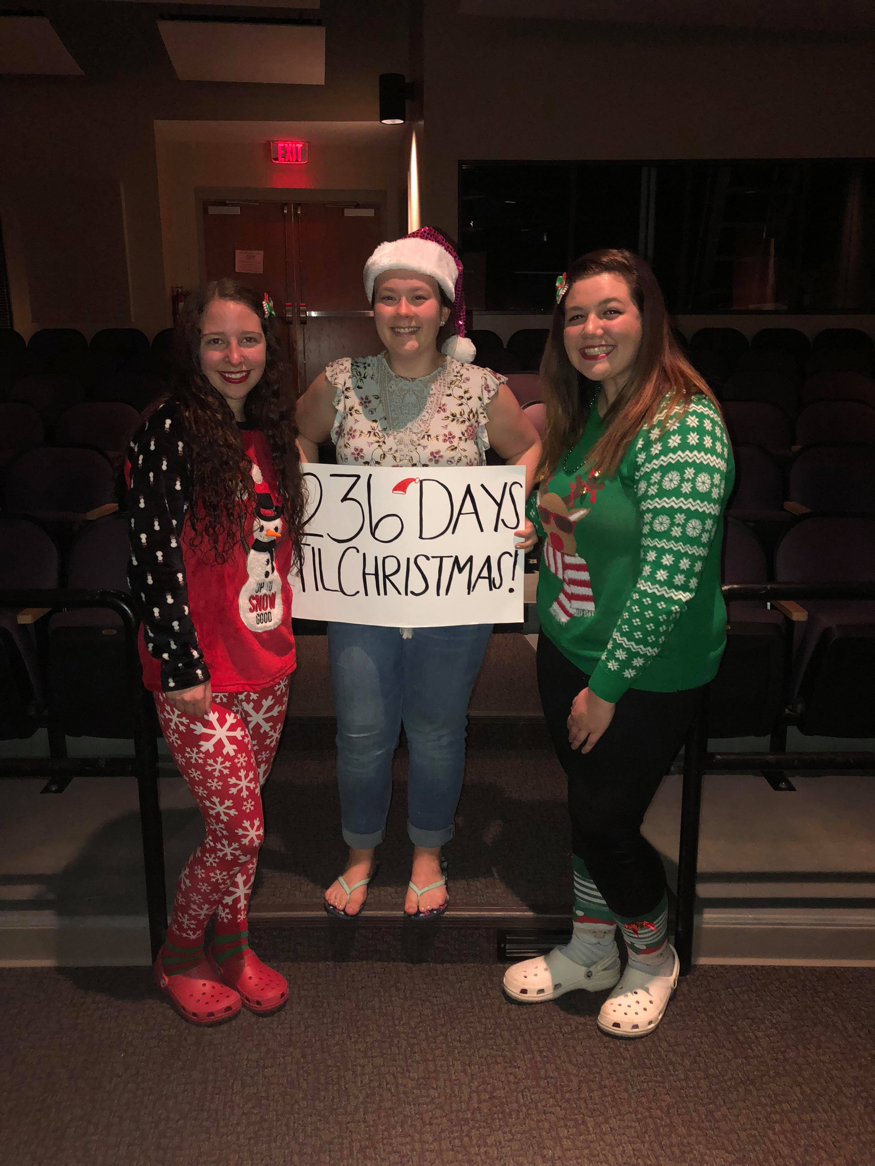 three girls in holiday pajamas holding poster that says 236 days until Christmas