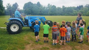 students gather around a farm tractor