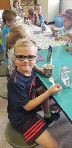boy with glasses eating sundae