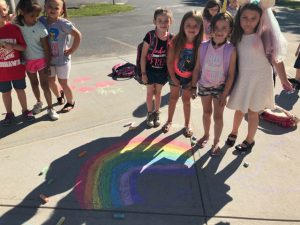 girls stand over chalk rainbow