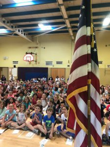 students sit before Flag in Glebe gym