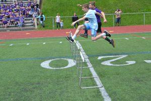 students jumping hurdles