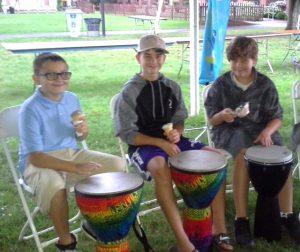 three boys sit behind drums
