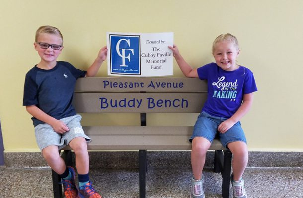 two Pleasant Ave students sitting on bench and holding a sign saying thank you to Cubby Faville Fund