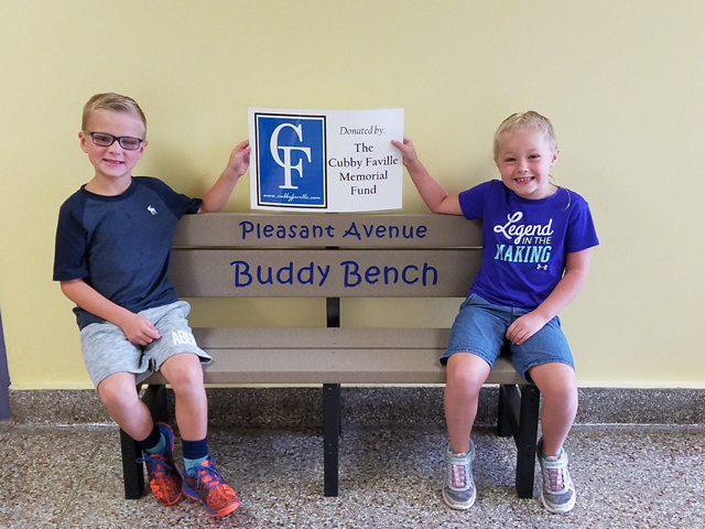 two Pleasant Ave students sitting on bench and holding a sign acknowledging Cubby Faville donation