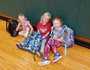 three students sitting on floor