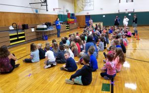 students seated on gym floor to watch zoomobile presenter