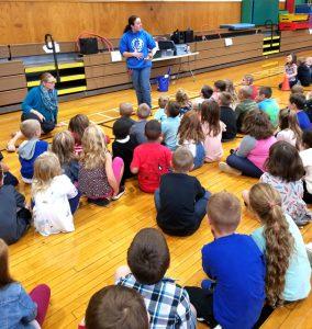 children seated on floor as presenter talks