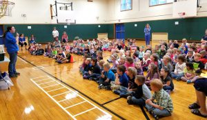 students sit on gym floor to watch zoomobile presenter