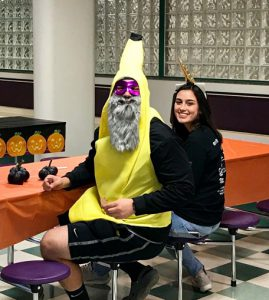two high school students at cafeteria table, one in a banana costume and a beard