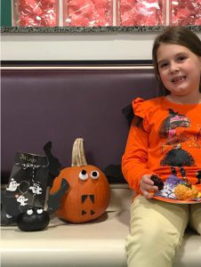 Glebe student sitting next to two decorated pumpkins