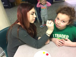 one student face painting another