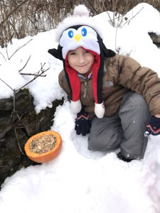 student kneeling in snow next to seed filled pumpkin