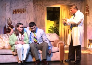 two characters sitting on sofa, third character in lab coat stands nearby
