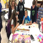 teacher and students work on crafts at a table