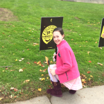 student kneeling by sign