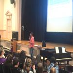 presenter speaking to students in auditorium