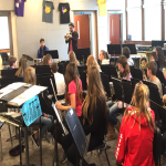 students in music room watch a performer