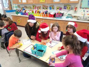 students gather around a table, some wearing Santa hats