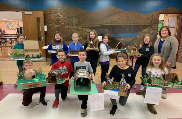 group of students in lobby holding dioramas