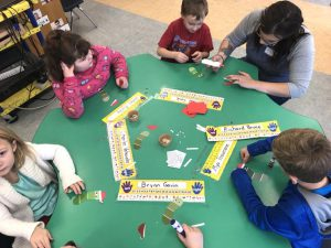 students sit at a table to play a game