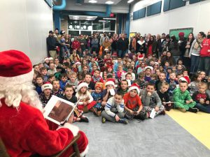 large group of children and parents listen to Santa reading a book