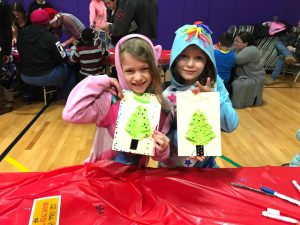 two students display Christmas tree crafts