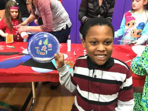 student holds up decorated plate