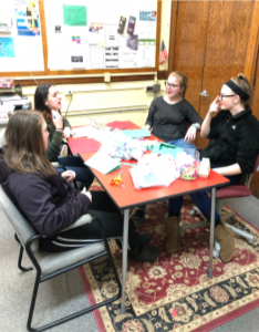 four students working on crafts