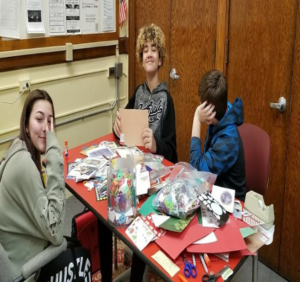 three students working on crafts