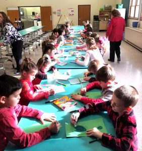 kids at cafeteria tables working on craft project