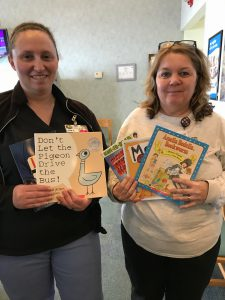 two JTA members holding children's books
