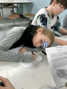 girl resting head on table while she writes