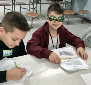 two boys engaged in writing, one wearing upside down sunglasses