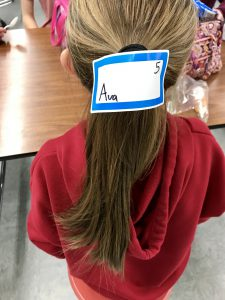 back of girls head with a sticker on her ponytail