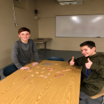 two students by table, one giving thumbs up