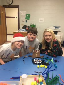 three students at a table, one wearing a Santa hat