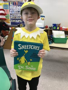 student dressed in Sneetch hat & shirt holds Sneetches book