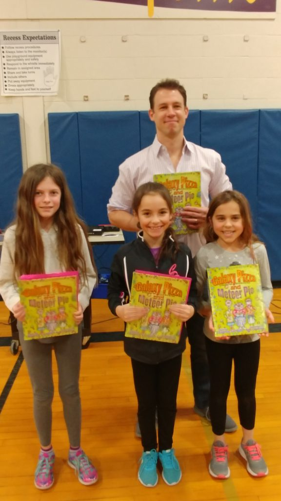 Mr. Sardelli with three students holding books