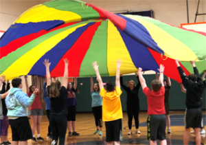 kids in circle with parachute billowing above