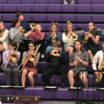 students with instruments on bleachers in JHS gym