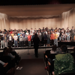 students perform vocals on stage in JHS PAC