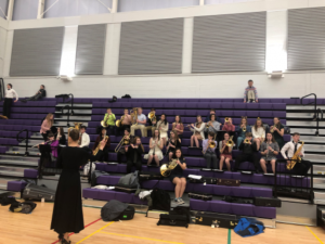 conductor leading students with instruments in JHS gym