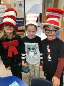 three students wearing Cat in the Hat headgear