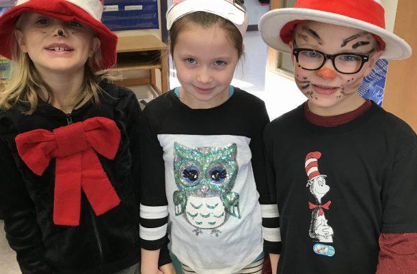 three students wearing Cat in the Hat headgear