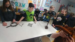 students examine animal trapping equipment